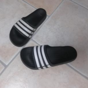 Adidas tofflor i stl 38. Svarta med vita stripes. Använda en sommar. Frakt 63 kr.