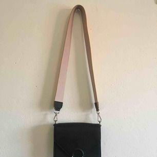 Väska från HM köpt för några månader sedan och knappt använd. Gult band som går att byta ut och är ljusrosa på andra sidan. Frakten ingår!