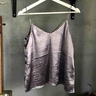 Superfint metalliskt linne med en snörning där bak! Finns lite lila toner i tyget 🌸 Aldrig använd då den inte sitter som jag vill🌸