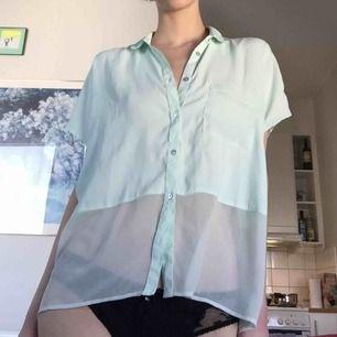 """Följsam mintpastellig blus, med ett transparent """"block"""" hela vägen runt, lagom balans mellan stilig och sexig, superskirt tyg som formar sig perfekt efter kroppen, känns sval och vacker. Säljes pga har tyvärr alldeles för många mintfärgade plagg..."""