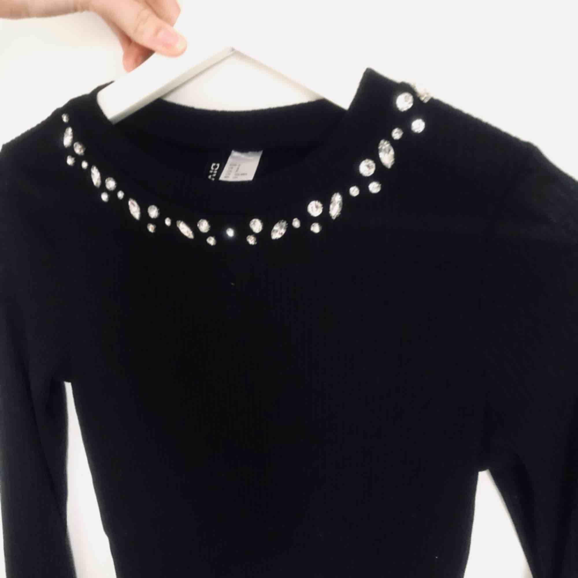 En svart långärmad tröja med glitterpaljetter i urringningen. En tunn och skön topp till fina tillfällen. Aldrig använd! För liten för mig och kan därför inte använda den. Köparen står för frakt. Toppar.