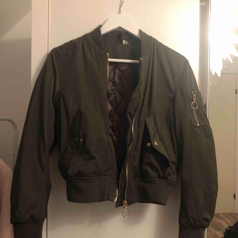 Militärgrön bomberjacka med guldiga detaljer. . Jackor.