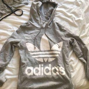 Grå adidas hoodie med fickor på sidorna. Knappt använd och ser helt ny ut. Orginalpris 699kr