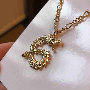 Guldigt halsband med en drake med strass. Nyskick och oanvänt. Frakt ingår i priset