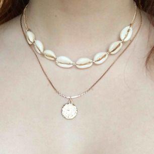 Flerradigt halsband med guldig medaljong, vita snäckor och guldiga kedjor! Jättefint och i nyskick. Frakt ingår i priset