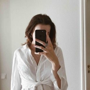 Vit skjorta med två band inbyggda som man kan knyta i midjan för att få skjortan mer formad efter kroppen. Knappt använd❤️