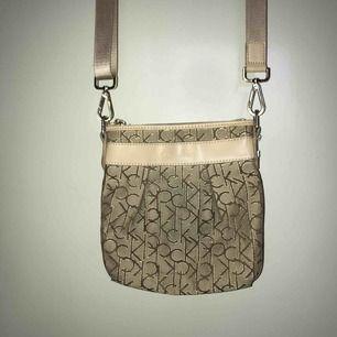 Calvin Klein väska med axelrem Väl använd och rätt sliten så säljer billigt! Hmu vid intresse!