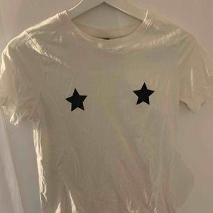 Vit T-shirt med svarta glitter stjärnor vid brösten. Strl Xs