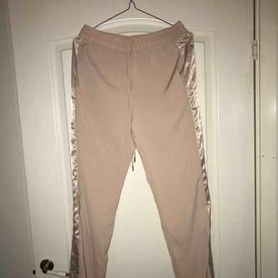 Kostym/joggers med glansig detalj på sidan. Superfina men fel passform på mig tyvärr. Använda en gång. Frakt ingår ej i priset