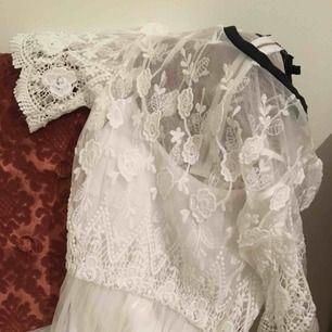 Klänning i spets med guldfärgad dragkedja baktill. En vit underklänning medföljer.   Kan hämtas i Hornstull, annars står köparen för fraktavgiften