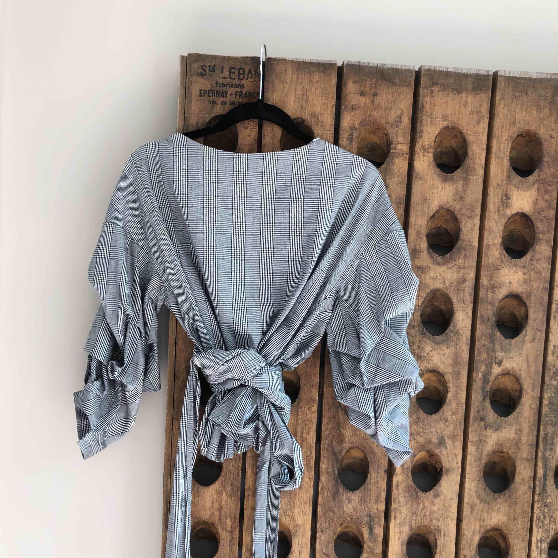 Rutig blus med långa omlottband som kan knytas på olika vis. 3/4 rynkad ärm  Midjekort Normal stl M Köpt på Zara Som ny! Frakt inkluderad. Blusar.