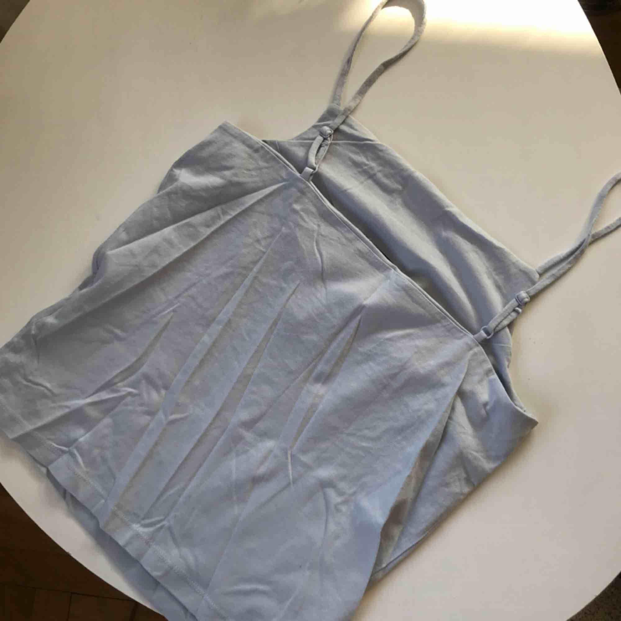 """Pastell-blått linne, aldrig använt. Med """"innanfoder"""" så att det sitter väldigt snyggt utan BH.. Toppar."""