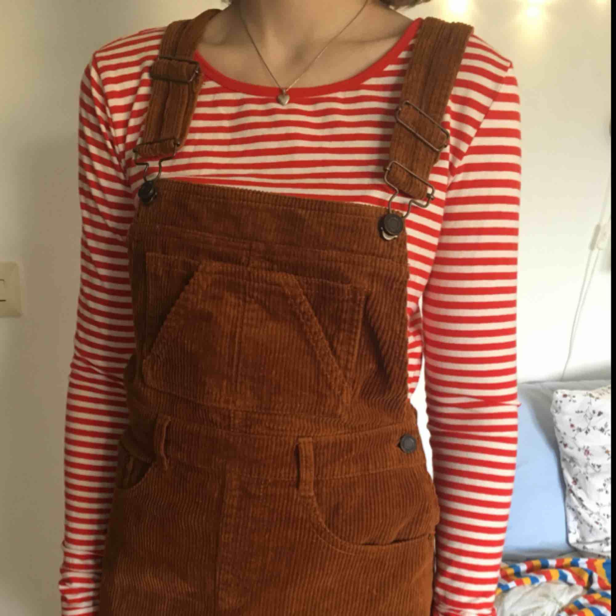 Rostfärgad manchester-hängselklänning från Pull and Bear, använd knappt tre gånger. Fickor både fram och bak, se längd på sista bilden. Kan både mötas upp i Stockholm och posta, men då står köparen för frakt! :) . Klänningar.