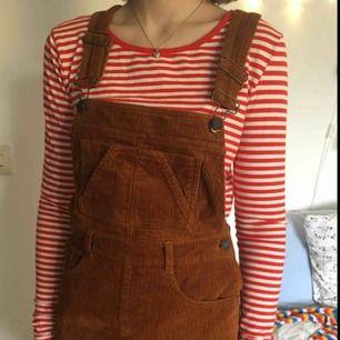 Rostfärgad manchester-hängselklänning från Pull and Bear, använd knappt tre gånger. Fickor både fram och bak, se längd på sista bilden. Kan både mötas upp i Stockholm och posta, men då står köparen för frakt! :)
