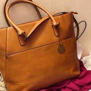En ljus brun stor väska har många fickor säljer den för 150 kr.  Finns i västerås att hämta men kan fraktas oxå men i så fall ska köparen betala frakten.