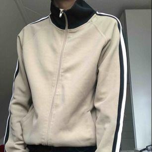 En beige tracktop från Marwin Heroes med en vit rand på sidan. Det står i tröjan att den är XL, men jag skulle säga att den är en S. Möts upp i Stockholm eller köparen står för frakt