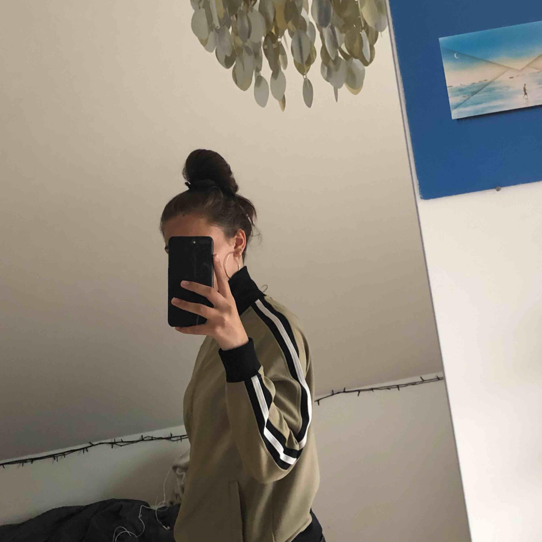 En beige tracktop från Marwin Heroes med en vit rand på sidan. Det står i tröjan att den är XL, men jag skulle säga att den är en S. Möts upp i Stockholm eller köparen står för frakt. Huvtröjor & Träningströjor.
