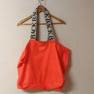 Ann-Sofie Back neon orange logo tote med dragkedjeförsedd innerficka. Har varit en favoritväska och är i begagnat skick, handtaget har blivit lite nopprigt av att fastna i kardborren. Nypris 1299 kr, ovanlig färg som inte går att få tag i längre. Frakr 55 kr.