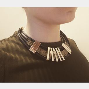 Fint halsband i läderimitation med gulddetaljer, passar bra till både vardag och fest. Säljes begagnat.