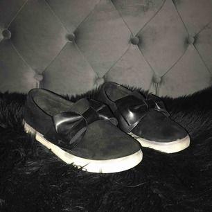 """Jätte fins slip on skor svarta med rosett, som dessutom är använda vid """" finare """" tillfällen. Säljs pga för små :/  Köpare står för frakten :)"""
