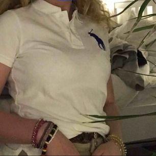 Cool t-shirt med ett lite större ralph lauren märke på ena bröstet, varsin liten slits på sidorna