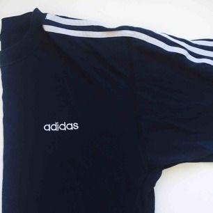 Oversized Adidas t-shirt, mörkblå med vita detaljer, köpt vintage. Bra skick, avklippta nedtill av förra ägaren. Passar som XS-M. Säljer för 50kr + eventuell frakt.