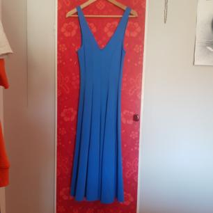 Blå strechig figursydd klänning med öppen rygg, v-ringad. Stl 40. Köpt på H&M, använd 1 gång.