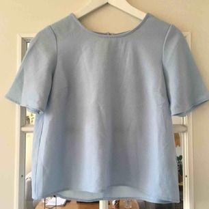 En pastellblå blus/topp. Frakt: 36 kr