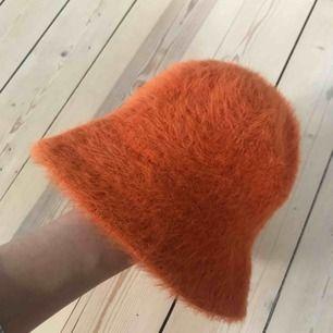 Orange Bucket hat, i lurvigt tyg. Påminner väldigt mycket om de hypade Kangol-mössorna. Använd en gång.