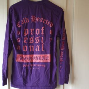 Bild 1 är baksidan på tröjan.  Lila tröja med rosa text. Avklippta lappar men tror den är köpt på carlings ⭐