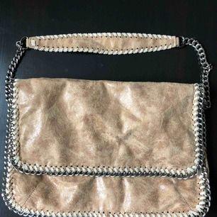 Ljusbrun/beige kedjeväska som knappast är använd och i jättebra skick! Ryms mycket men är även jättefin och perfekt nu till sommaren.