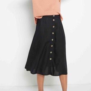 Ljuvlig svart kjol i viskos, storlek medium. Fint fall, resår baktill i midjan, träknappar längst hela fram. Nyskick! Gratis frakt, har swish!