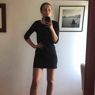 Svart kort klänning med dragkedja i bak och trekvarts ärmar. Stl S  Säljer för att den är för kort (jag är 174 cm). Köpare står för frakt.