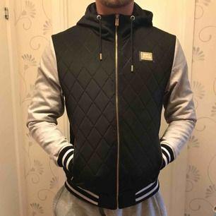 Jacka från Supply & Demand. Jackan är svart med gråa ärmar och guldiga detaljer och har huva. Bra skick och perfekt för våren
