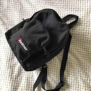 Svart Eastpak miniryggsäck i Mycket fint skick! Köpt på Hollywood Sthlm. Höjd ca 28cm, bredd ca 23cm, botten ca 14cm