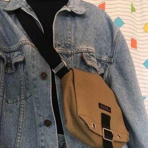Jättesnygg ♻️vintage♻️ y2k väska i en beige färg 🍯 kan stajlas med en denim on denim look och svarta boots 😍 Frakten ligger på 36kr 📨 Bandet kan justeras mellan 77 och 147cm, Den har tre fack 😜