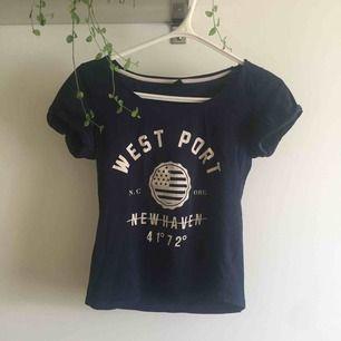 Marinblå figursydd t-shirt med tryck och uppvikta ärmar.