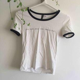 """Vit tight t-shirt med texten """"you are your own beautiful"""" och svarta kanter runt ärmar och hals. Sitter superfint och bekvämt. Längst ner finns ett litet litet hål i tyget (bild 3) men verkligen inget man tänker på."""