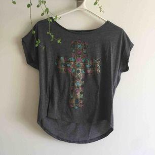 """Grå slapp T-shirt med guldigt kors med tryckta """"stenar"""" på. Sitter enligt mig snyggare om man knyter eller stoppar in tröjan."""