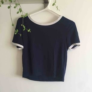 Mörk/marinblå lite croppad t-shirt med vita kanter runt ärmar och hals. Sitter bekvämt och fint.