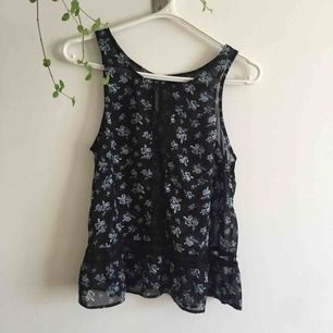 Svart lite genomskinligt linne med blå blommor och spets i en strimma runt midjan och rakt upp från naveln ända upp till halsen.