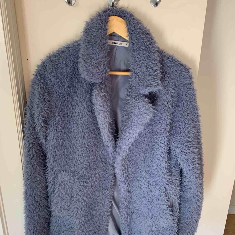 Längre fluffig jacka i blå färg från Gina!  Storlek 36. Använd 6-7ggr.. Jackor.