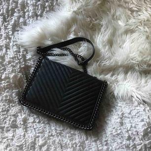 En svart väska med kedjeaxelband. Fint skick. Frakt tas vid köp.