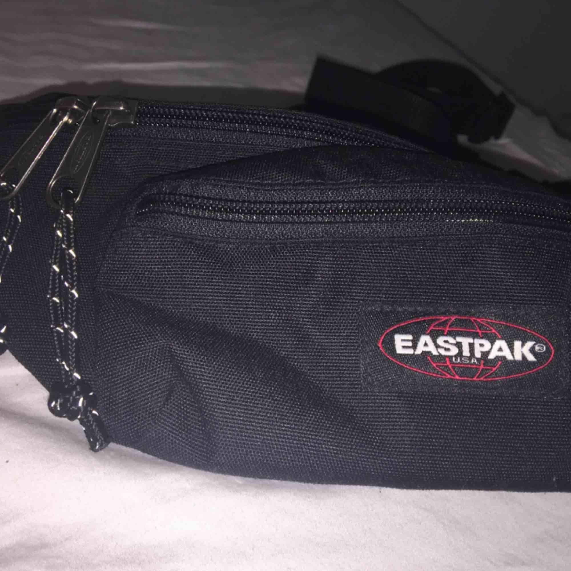Svart Eastpak midjeväska med anpassningsbar storlek på remmen och två fack. Ett stort och ett litet. Väskan är använd några få gånger och fortfarande i nyskick. Köparen betalar frakt. Väskor.