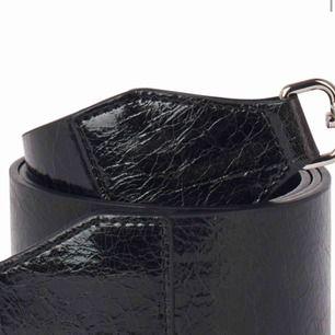En väska från dondonna med ett tjockt glansigt, spräckligt  axelband från Åhléns.
