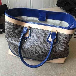 BUD PÅ TRADERA på Lovisafridelina. Aldrig använd! En äkta DKNY handväska. Deras logo som mönster. I väskan finns det öppna fack för mobil eller nycklar. Finns en ficka som går att försluta. Väskan går att försluta av en magnet längst upp.