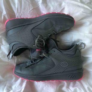 Jättefina gråa sneakers med rosa sula från heelys! Använda ett fåtal gånger, platta man kan sätta istället för hjul så det blir en vanlig sko medföljer. Kan eventuellt byta skorna mot ett par andra heelys, säljer pga rosa är inte min färg