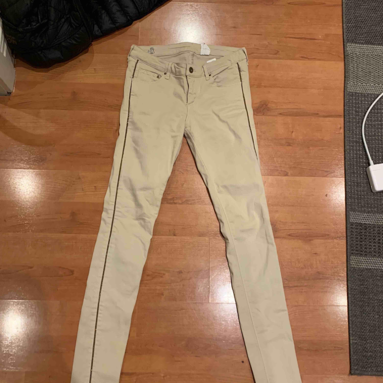 Heeelt nya beiga byxor från H&M. Cool detalj på sidan. Aldrig använda & har bara legat i garderoben, inköpspris 399kr. 30/34. Fynda!!. Jeans & Byxor.