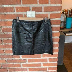 Läder kjol svart, längd 40 cm, låg midja, fint skick, litet sprund fram över vänster ben.