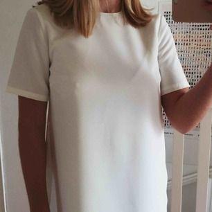 Enkel vit klänning i rak modell, köpt på Nelly.com förra året till min student, men använde den aldrig. Den är därför helt ny, endast provad. Kostade 300kr. Slutar en bit ovanför knäna på mig som är 1,63cm. Dubbelt tyg gör att den inte är genomskinlig.